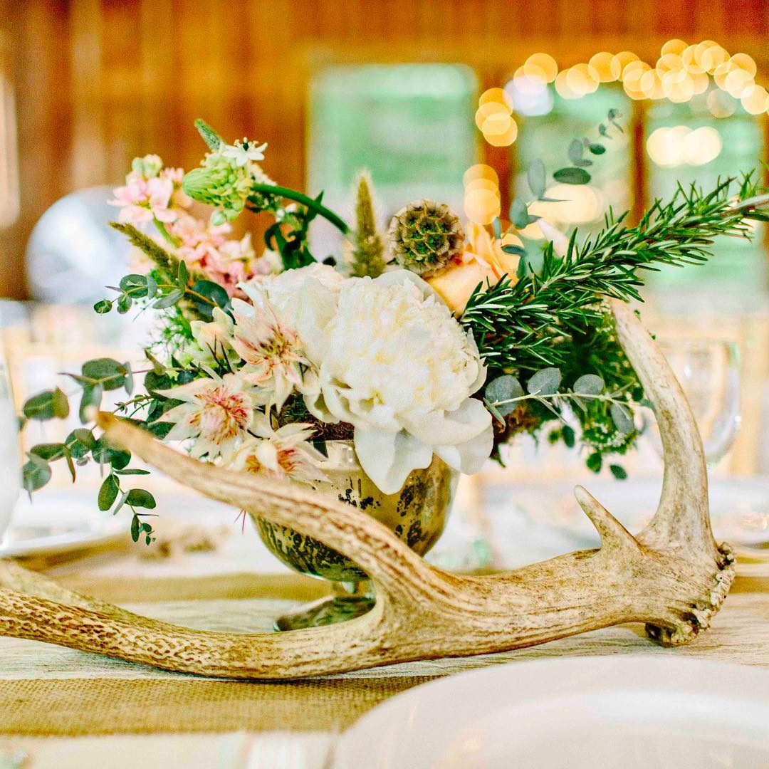 {table bling} photo | @kellydillonphotography  #antlers #centerpiece #rustic #barnwedding #rusticelegance #mercuryglass #rosemary #peony #blushingbrideprotea #weddingflorist #lotusfloraldesigns