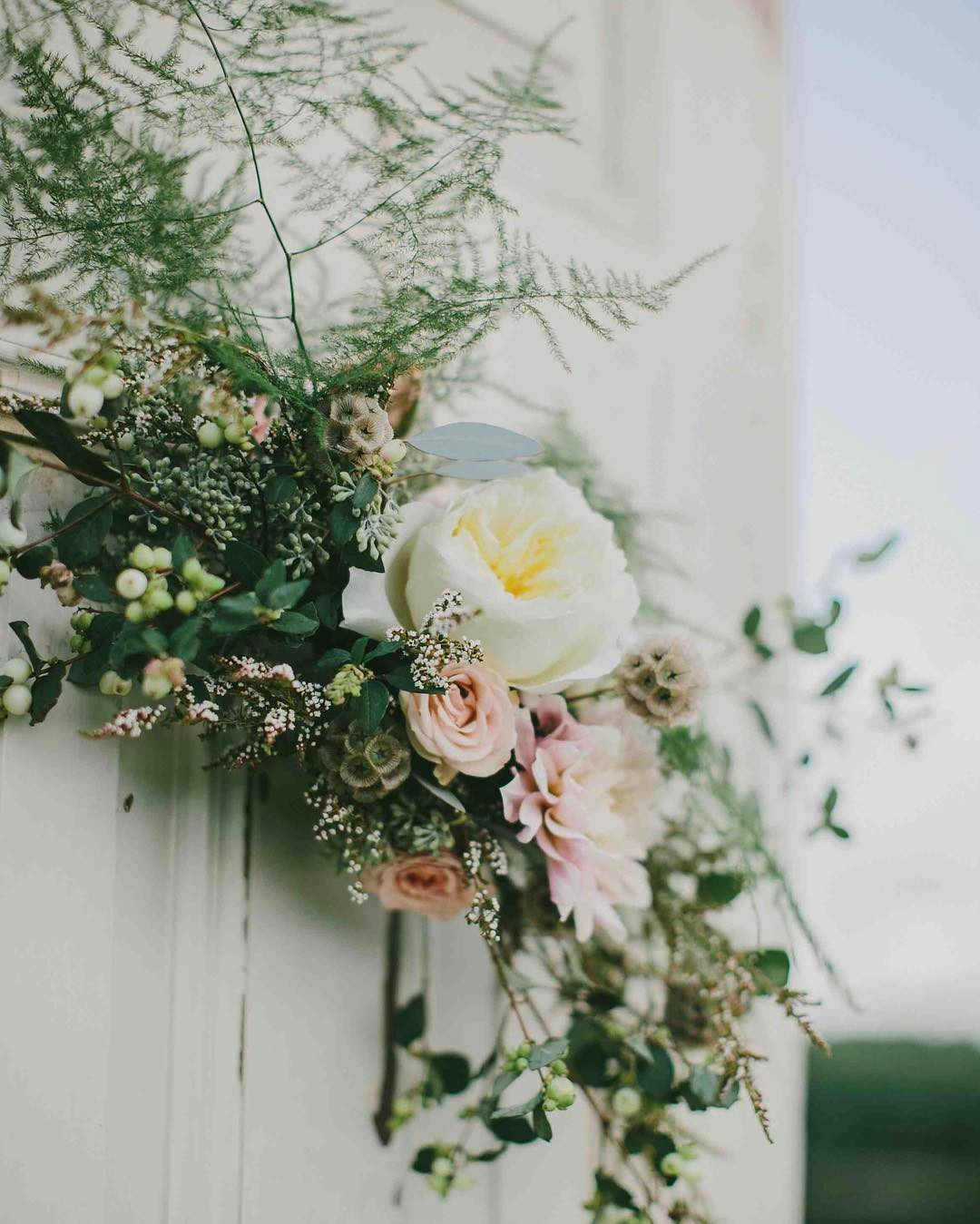 {flower love on reclaimed vintage door} photo | @emilydelamater  #kitzfarm #ceremony #vintagedoors #ceremonydecor #flowerswag #weddingflorist #flowerartist #lotusfloraldesigns #flowerlover