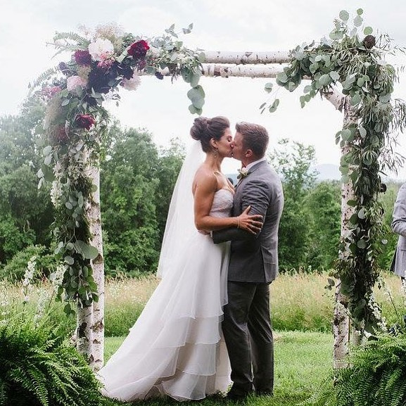 {sealed with a kiss} photo | @bethanyanddan  #husbandandwife #forever #ceremony #arbor #arborflowers #ferns #eucalyptus #peony #smokebush #prettyflowers #lovely #rustic #rusticwedding #lotusfloraldesigns #weddingflorist #weloveflowers
