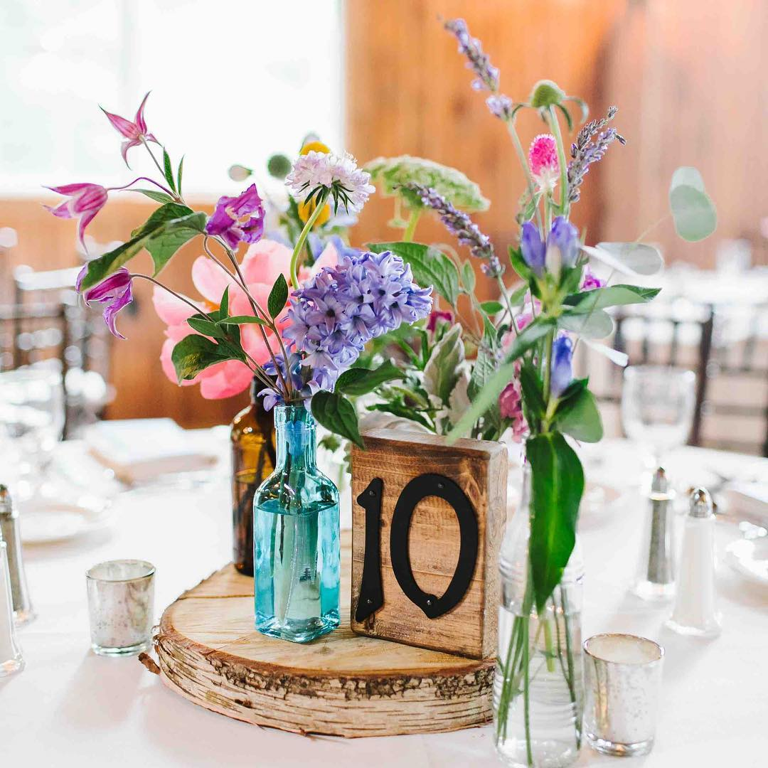 Vintage bottles with pretty blooms never goes out of style?? . photo | @emilytebbetts . . #tabledecor #prettyflowers #centerpiece #rustic #vintage #barnwedding #birch #woodslice #repurposed #aqua #pastels #nhwedding #lotusfloraldesigns #lakeside