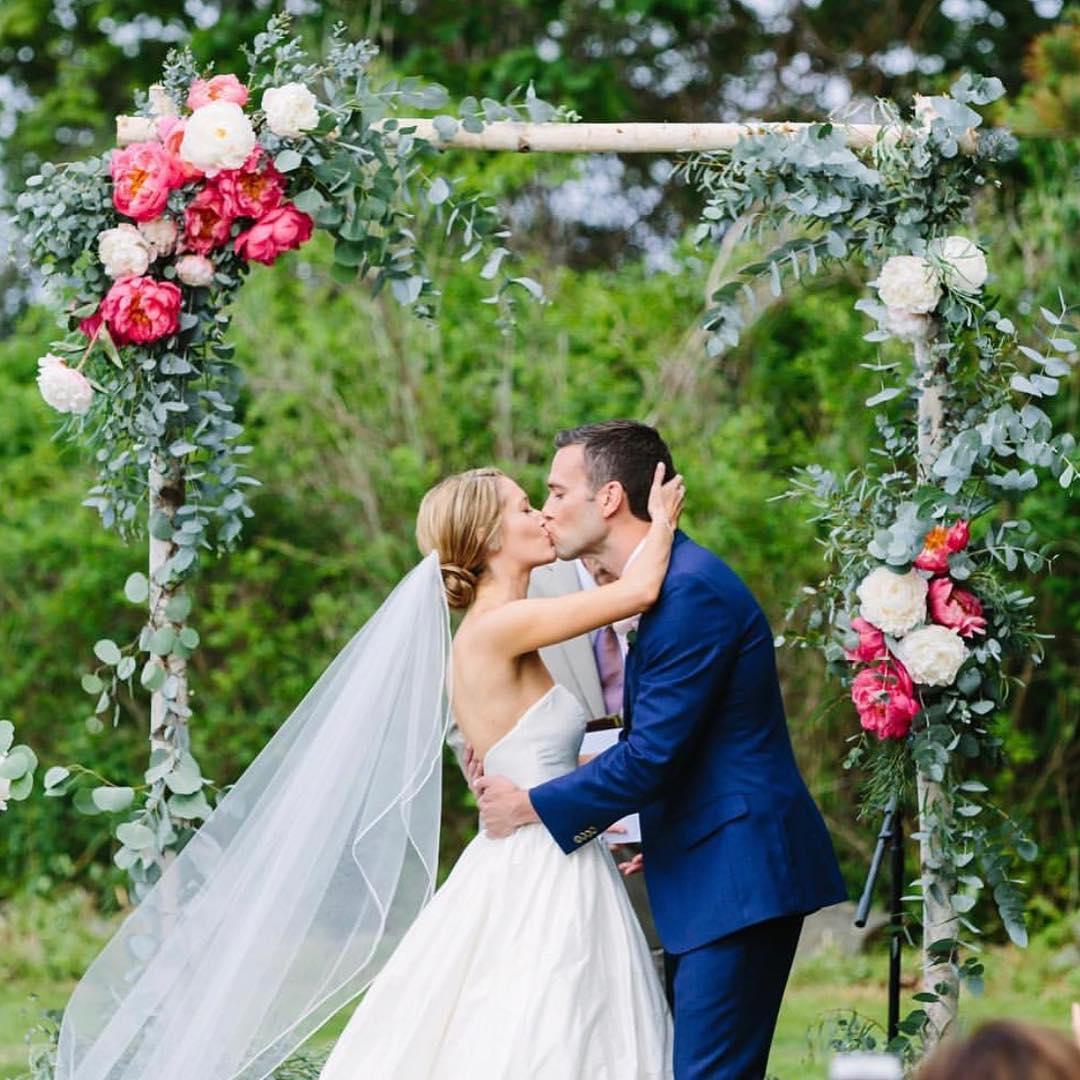 {sealed with a kiss} photo | @rachelbuckleyweddings . . . #husbandandwife #ido #firstkiss #sweet #arbor #ceremony #ceremonydecor #backdrop #peonies #eucalyptus #coral #pink #whitebirch #lotusfloraldesigns #weddingflowers